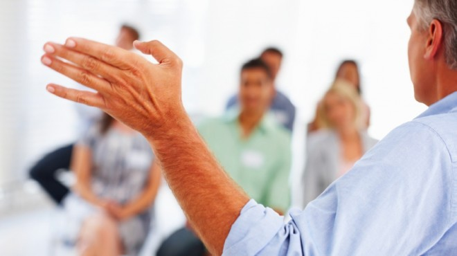 Mature business man giving presentation to group of people at seminar