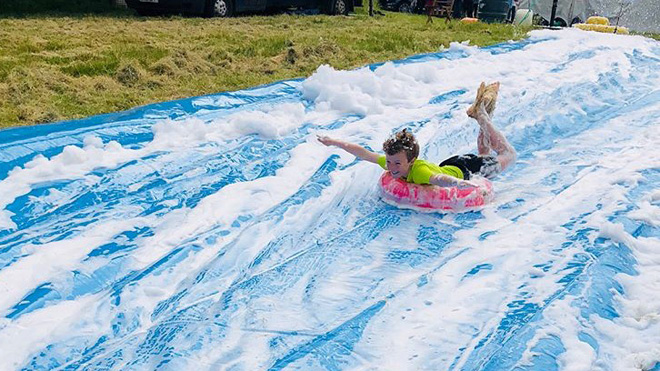 Child on the foam slip 'n' slide at the Scouts Fundays event.